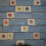 Frise en grès avec des carreaux bleu et des petits carreaux blanc cassé avec fleurs.